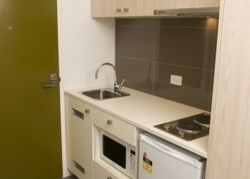 Kitchen with electric stove, fridge and microwave.